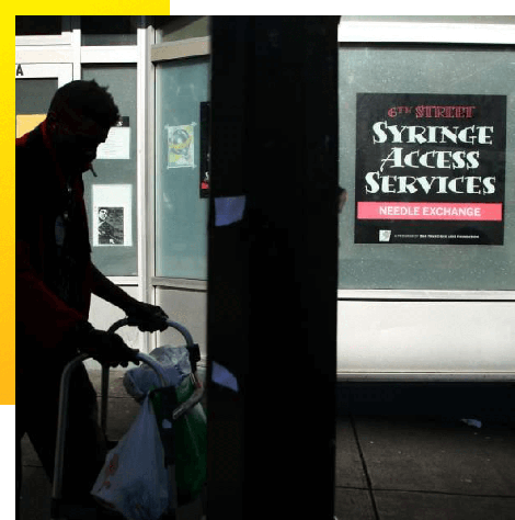 """photo of a man with a walker outside of a building with a sign that reads, """"6th Street Syringe Access Services, Needle Exchange."""""""
